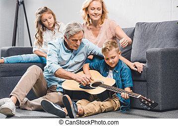 family playing on guitar