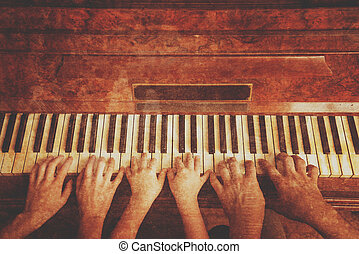 Family playing on piano - Family of three people is playing...