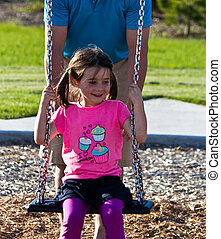 Family playing on the swing set