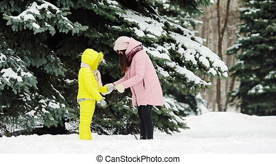 Family playing snowballs outdoors in winter day