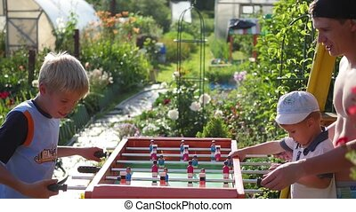 Family playing table football outdoors.Fun outdoors