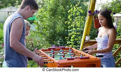 Family playing table football outdoors. Fun outdoors