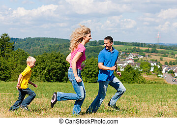 Family playing tag on meadow in summer