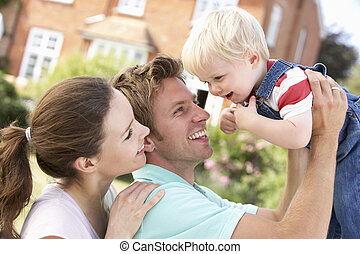 Family Playing Together In Garden At Home