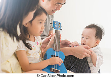 Family playing ukulele at home