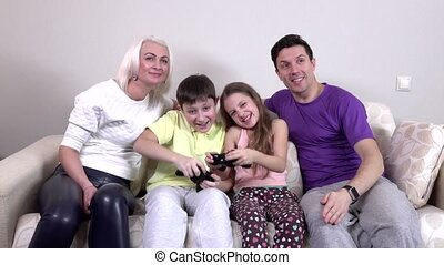 Family playing video games in the living room, slowmotion -...