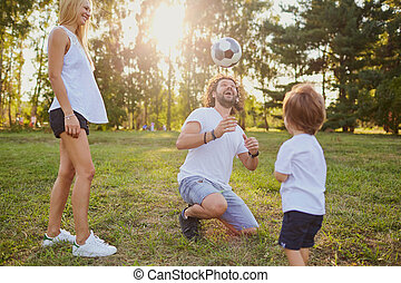 Family playing with a ball in the park.