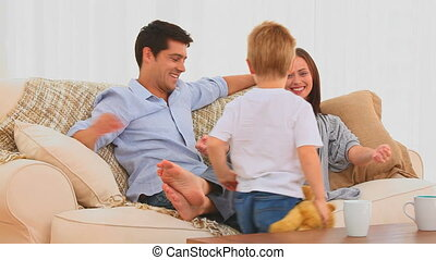 Family playing with a teddy bear on their living room