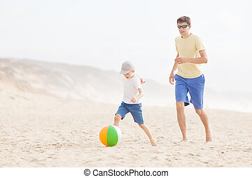 family playing with ball at the beach