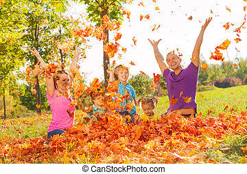 Family playing with leaves and throwing them