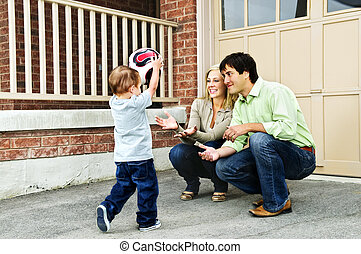 Family playing with soccer ball - Happy young family playing...
