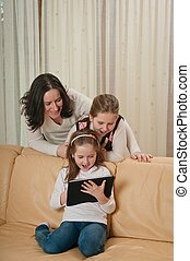 Family playing with tablet at home