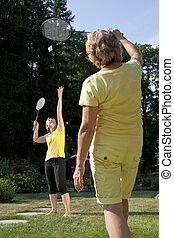 family plays badminton in the garden