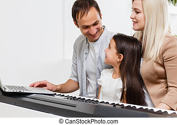 family plays the digital piano at home, learning online, family rest during quarantine, self-isolation, online education concept. support for loved ones concept