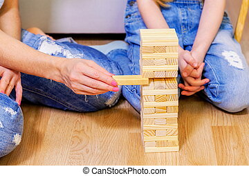 Family plays wooden tower game of wood sticks