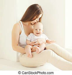Family portrait of happy young mother kissing cute baby at home in white room near window