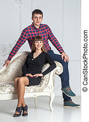 Family portrait of  young couple sitting on a couch