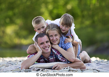 Family portrait of young happy mother, father and two cute blond children, boy and girl on bright summer day with green bokeh background. Happy family relations, love, care and perfect holiday concept