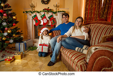 Family posing at living room decorated for Christmas with burning fireplace