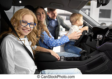 Family posing in car cabin of new automobile.