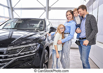 Family posing near black auto in dealership showroom.