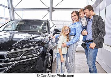 Family posing near black auto in dealership showroom.