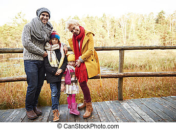 Family posing on wooden bridge