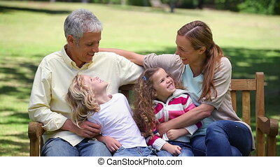 Family posing together on a bench in a park