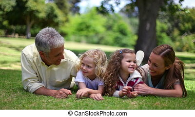 Family posing together while lying on the grass