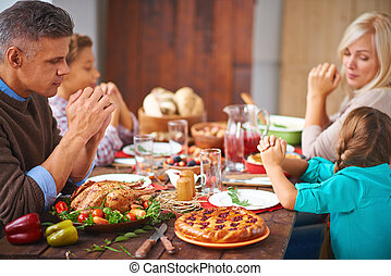 Family pray - Portrait of modern family of four sitting at...