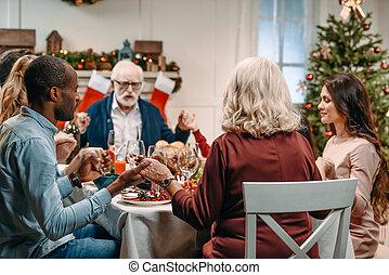 family praying before christmas dinner