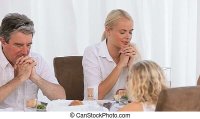Family praying before dinner in the dinning room
