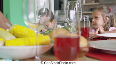 Family praying before having lunch on dining table at home 4k