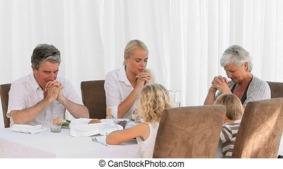 Family praying before lunch