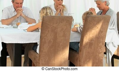 Family praying before lunch in the dinning room