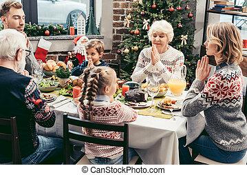 family praying on christmas dinner