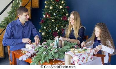 Family preparing christmas gifts in domestic room - Positive...