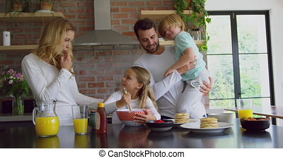 Family preparing food on worktop in kitchen at comfortable home 4k
