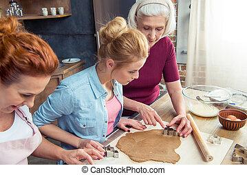 Family preparing gingerbread cookies