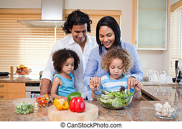 Family preparing salad together in the kitchen