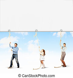 Family pulling banner - Image of young happy family pulling...