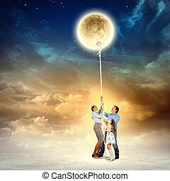 Family pulling moon