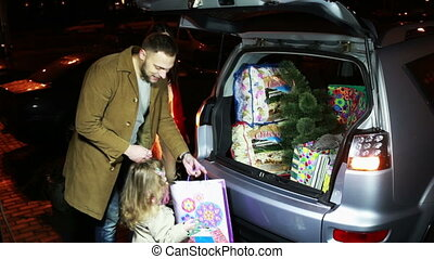 Family puts Christmas gifts and tree in the car
