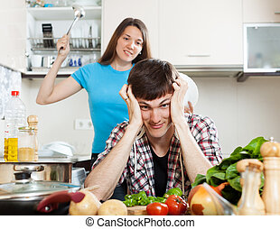 Unhappy young man with angry wife at home