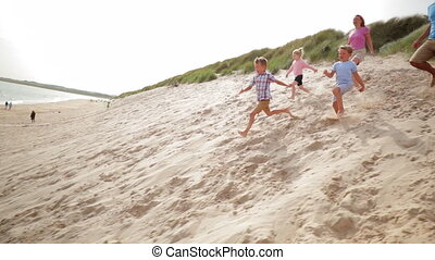 Family Racing Down a Sand Dune - Slow motion shot of a ...