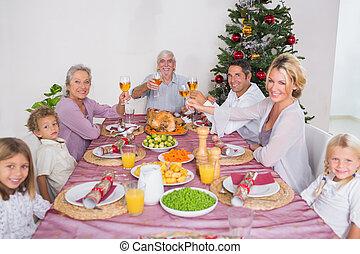 Family raising their glasses at christmas