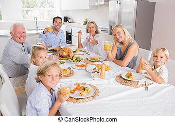 Family raising their glasses at thanksgiving