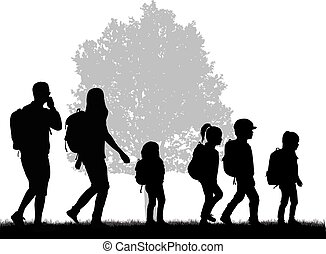 Family reaching with backpacks on a trip.