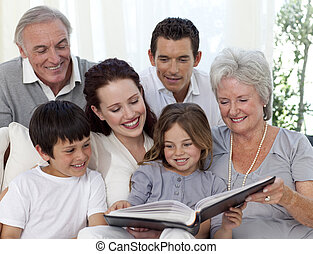 Family reading a book in living-room