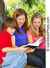 Family reading a book - Family of mother and children...